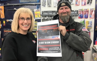 "Pam Anderson from Lakefield Auto Parts store congratulates Darren Henry of ABC Customs, a customer of Peterborough Automotive, on winning the $1,000 runner-up prize in this year's Professionals' Choice Auto Parts ""Win a Harley Sportster"" promotion."